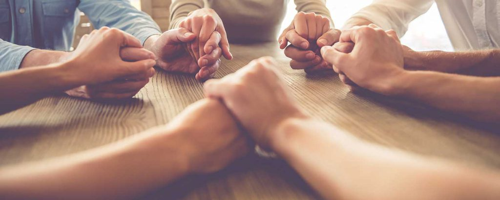 a photo of people sitting at a table holding hands and praying